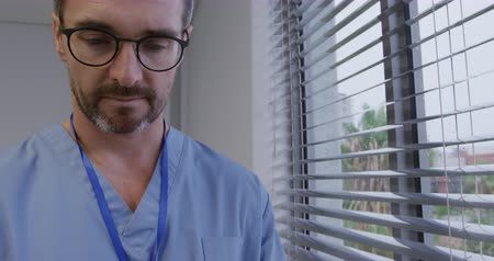 hemşire : Front view close up of a Caucasian male healthcare professional with a beard, wearing glasses and scrubs using a smartphoen and looking out of the window at a hospital, slow motion