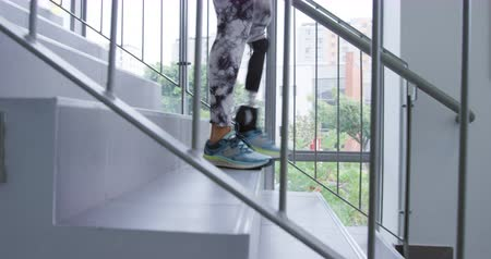 opção : Side view low section of a Caucasian female patient with a prosthetic leg walking down a staircase at a hospital, for rehabilitation practice and exercise Stock Footage