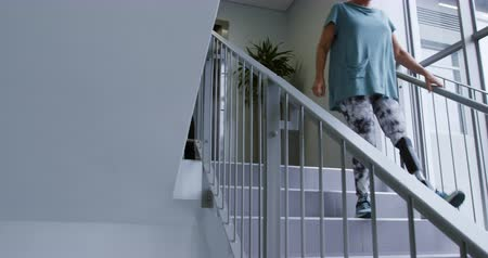 opção : Front view of a Caucasian female patient with a prosthetic leg walking down a staircase at a hospital, for rehabilitation practice and exercise