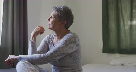 mento : Side view of a senior Caucasian woman with short grey hair sitting on her bed with her hand under her chin, looking out of the window at home and stretching, slow motion Filmati Stock