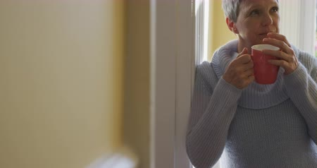 isolamento : Front view of a senior Caucasian woman with short grey hair wearing a cowl neck sweater at home, standing in her house leaning in a doorway, drinking a cup of coffee and smiling, slow motion Vídeos
