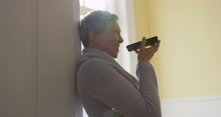 kısa : Side view of a senior Caucasian woman with short grey hair at home, standing in her home wearing a cowl neck sweater, leaning against a wall by a window talking on a smartphone and laughing, slow motion