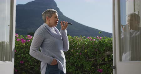 liga : Side view of a senior Caucasian woman with short grey hair at home, standing in her garden wearing a cowl neck sweater holding and talking on a smartphone, seen from the open doorway of her house, with flowers and a mountain view in the background, slow m Vídeos