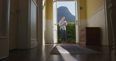 kapualj : Front view of a senior Caucasian woman with short grey hair at home, standing in her garden wearing a cowl neck sweater talking on a smartphone, seen full length, from the hallway, through the open doorway of her house, with flowers and a mountain view in Stock mozgókép