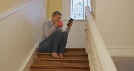 duševní : Low angle view of a senior Caucasian woman with short grey hair at home, sitting on the stairs wearing a cowl neck sweater, drinking a cup of coffee and using a smartphone, slow motion Dostupné videozáznamy