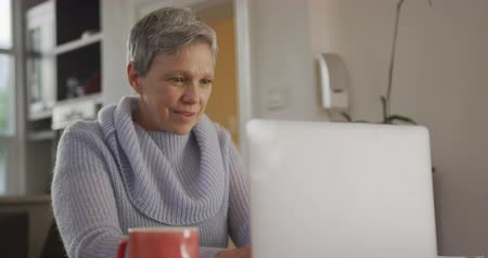 necked : Front view close up of a mature Caucasian woman with short grey hair wearing a cowl necked sweater sitting at her dining room table using a laprop computer and smiling, slow motion