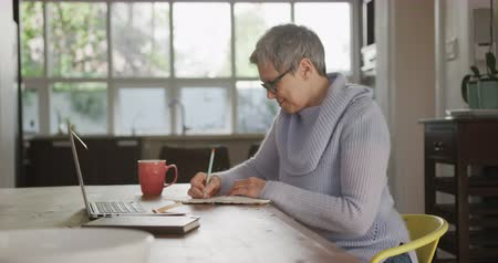 necked : Side view of a mature Caucasian woman with short grey hair wearing a cowl necked sweater and glasses, sitting at her dining room table writing in a notebook and smiling, a laprop computer on the table in front of her, slow motion