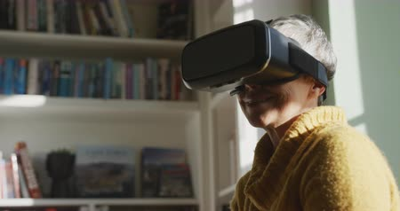 kısa : Side view close up of a senior Caucasian woman with short grey hair wearing a cowl neck sweater at home, wearing a VR headset and smiling, a window behind her, slow motion Stok Video
