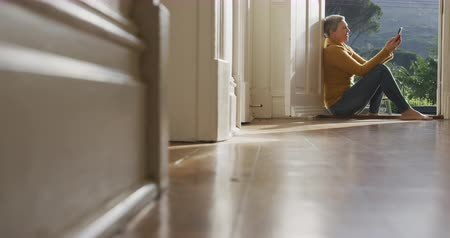 deuropening : Side view of a senior Caucasian woman with short grey hair at home, sitting in the hallway by the open front door using a smartphone, slow motion Stockvideo