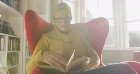 сосредоточиться на переднем плане : Front view of a senior Caucasian woman with short grey hair at home, wearing a cowl neck sweater and reading glasses, sitting in a wingback armchair and reading a book, backlit by sunlight from a window, slow motion