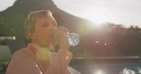 focussed : Side view of a senior Caucasian woman with short grey hair wearing sports sitting and drinking a bottle of water by the swimming pool in her garden after exercising, with a rural view in the background, backlit by sunlight, slow motion