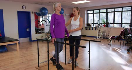paralelo : Side view of a senior Caucasian woman exercising at a sports centre gym with a Caucasian female physiotherapist guiding her through an exercise programme, walking between parallel bars Vídeos