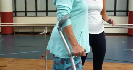 amputee : Side view of a Caucasian woman with a prosthetic leg walking on crutches at a sports centre gym with a Caucasian female physiotherapist guiding her through an exercise programme Stock Footage