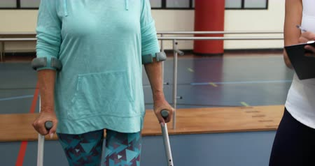 kule : Front view of a Caucasian woman with a prosthetic leg walking on crutches at a sports centre gym with a Caucasian female physiotherapist guiding her through an exercise programme holding a clipboard Wideo