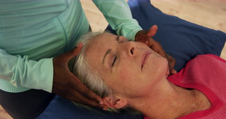 physiotherapy : High angle close up view of a senior Caucasian woman lying on an examination couch at a sports centre gym with an African American female physiotherapist holding her head in both hands and moving it gently from side to side