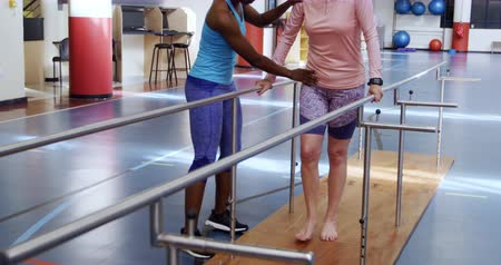 paralelo : Front view of a senior Caucasian woman exercising at a sports centre gym with an African American female physiotherapist guiding her through an exercise programme, walking between parallel bars Vídeos