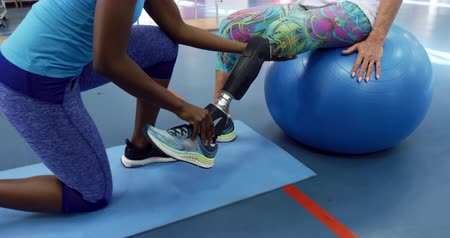 a genoux : Low section side view of a Caucasian woman with a prosthetic leg sitting on an exercise ball at a sports centre gym wearing sports clothes, with an African American female physiotherapist kneeling and helping her to move her prosthetic leg Vidéos Libres De Droits