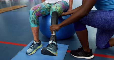 ajoelhado : Low section front view of a Caucasian woman with a prosthetic leg sitting on an exercise ball at a sports centre gym wearing sports clothes, with an African American female physiotherapist kneeling and helping her to move her prosthetic leg Vídeos