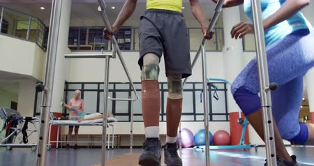 ajoelhado : Low section front view of an African American man with prosthetic legs at a sports centre gym wearing sports clothes, with an African American female physiotherapist kneeling and helping him to walk holding parallel bars Vídeos