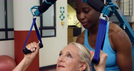lift ups : Front view of a Caucasian woman lying on an examination couch at a sports centre gym with an African American female physiotherapist helping her to exercise her arms using pull up straps Stock Footage