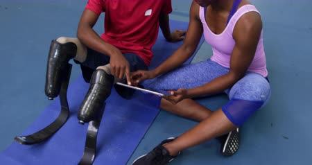 amputee : High angle front view of an African Amercian man with two prosthetic legs wearing sports clothes at a sports centre gym sitting on the floor and looking at a tablet computer with an African American female physiotherapist and smiling Stock Footage