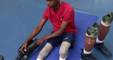 amputee : High angle front view of an African Amercian man with two prosthetic legs wearing sports clothes at a sports centre gym, sitting on the floor and removing his prosthtics and swapping them for another pair