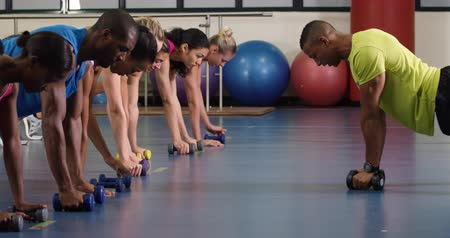 lift ups : Side view of an African American male fitness trainer instructing a diverse group of adults during a fitness class, lying with arms extended in a press up position raising dumbbells together Stock Footage