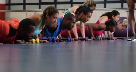 keep fit : Low angle view of an African American male fitness trainer instructing a diverse group of adults during a fitness class, walking past them as they do press ups together Stock Footage