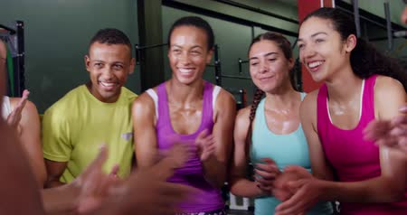 amontoado : Front view close up of a diverse group of adults after a fitness class at a sports centre, clapping, smiling, going into in a huddle and giving each other high fives Stock Footage