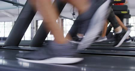four legs : Low section side view of three women wearing sports clothes exercising at a sports centre gym, running and walking on treadmills at different paces and speeds Stock Footage