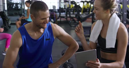 инструктор : Front view of an athletic Caucasian man and woman wearing sports clothes talking during a break from training at a gym, the has a towel around her neck and is showing the man a tablet computer, slow motion Стоковые видеозаписи
