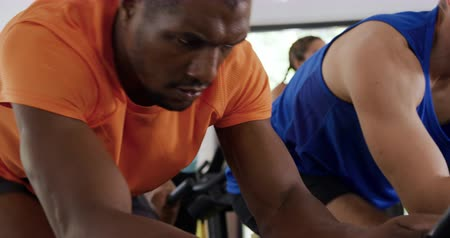 focussed : Side view close up of an African American man wearing sports clothes working out at a sports centre gym, cycling on a stationary exercise bike, with a diverse group of adults cycling in the background, slow motion