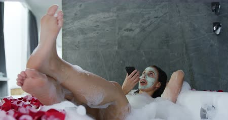 reclináveis : Front view of a young Caucasian woman wearing a face pack, lying back in a foam bath with her feet up talking on a smrtphone and smiling, slow motion