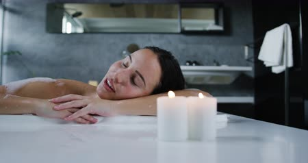 barre : Front of a young Caucasian woman with long dark hair relaxing in a foam bath with lit candles beside the bath, leaning on the side and resting her head on her arms with eyes closed, slow motion Vidéos Libres De Droits