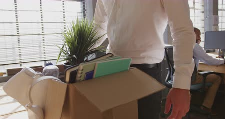 redundancy : Front view mid section of Caucasian creative professional man in a modern office leaving his job packing and carrying a cardboard box with his male colleague working in the background, slow motionx Stock Footage