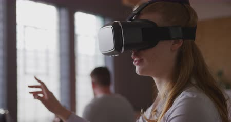 коллега : Front view close up of young Caucasian creative professional woman in a modern office wearing VR headset and touching virtual interactive screen with her colleagues in the background, slow motion