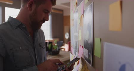 note de service : Side view of young Caucasian creative professional man in a modern office using tablet computer and writing on mood board, slow motion