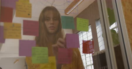 note de service : Low angle front view of young Caucasian creative professional woman in a modern office sticking memo notes on mood board, slow motion Vidéos Libres De Droits