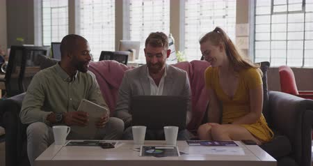 focussed : Front view of young Caucasian and mixed race creative professional men and young Caucasian creative professional woman in a modern office sitting on a sofa using laptop computer brainstorming, slow motion Stock Footage