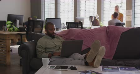 reclináveis : Front view of young mixed race creative professional man in a modern office reclining on a sofa using laptop computer with his colleagues in the background, slow motion