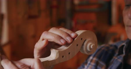 inacabado : Side view close up of a senior Caucasian female luthier working on an unfinished violin in her workshop, inspecting the neck and scroll Stock Footage