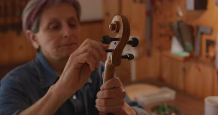 instrument maker : Front view close up of a senior Caucasian female luthier winding the strings on the tuning pegs on a finished violin in her workshop, inspecting the neck and scroll
