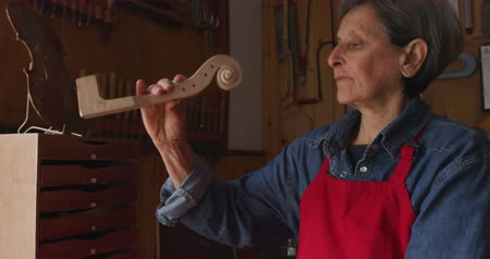 instrument maker : Side view of a senior Caucasian female luthier wearing an apron working on an unfinished violin in her workshop, inspecting the neck and scroll Stock Footage
