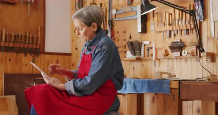 instrument maker : Side view close up of a senior Caucasian female luthier wearing a red apron sitting on a stool at her workshop using a tablet computer and thinking, with tools hanging up on the wall in the background.