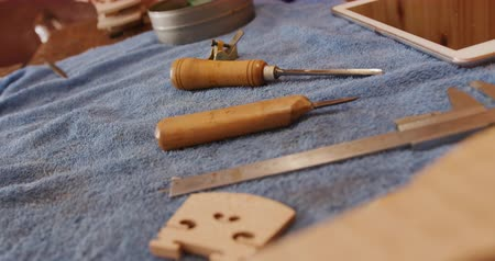 изделия из дерева : Close up of tools, a notebook and the unfinished neck and scroll of violin on a workbench at the workshop of a luthier Стоковые видеозаписи