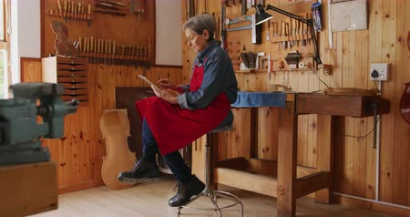 instrument maker : Side view of a senior Caucasian female luthier wearing a red apron sitting on a stool at her workshop using a tablet computer, with a workbench and tools hanging up on the wall in the background.