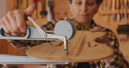 bitola : Front view close up of a senior Caucasian female luthier working on a violin at her workshop, using a tool to check the thickness of the front of the violin, with tools hanging up on the wall in the background.