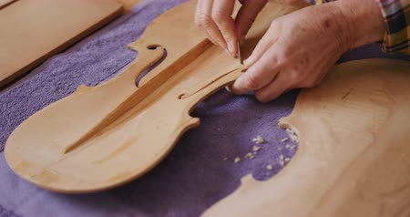 instrument maker : Close up of the hands of a senior Caucasian female luthier working on a violin at a workbench in her workshop, shaping the inside of the front panel of a violin with a sharp blade, slow motion. Stock Footage