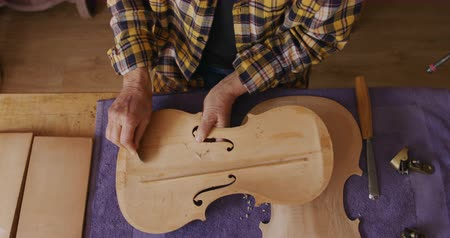 instrument maker : Overhead view of a senior Caucasian female luthier working on a violin at a workbench in her workshop, shaping the inside of the front panel of a violin with a sharp blade, slow motion. Stock Footage