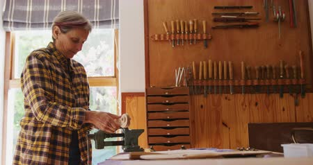 instrument maker : Side view of a senior Caucasian female luthier at a workbench in her workshop, clamping a violin neck in a vice in order to work on it, with tools hanging up on the wall in the background, slow motion